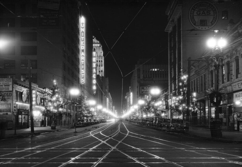 A 1930 view looking north on Broadway from 10th Street. Ornamental streetlights illuminate the trolley tracks.