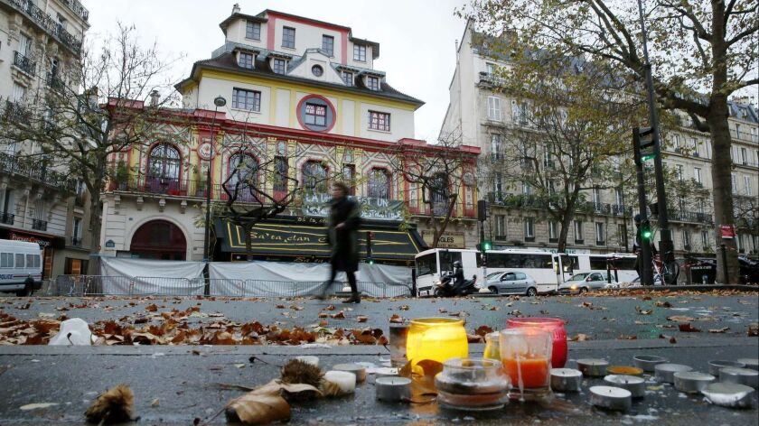 A woman walks past the Bataclan concert hall in Paris, the site of a deadly terror attack in November 2015.