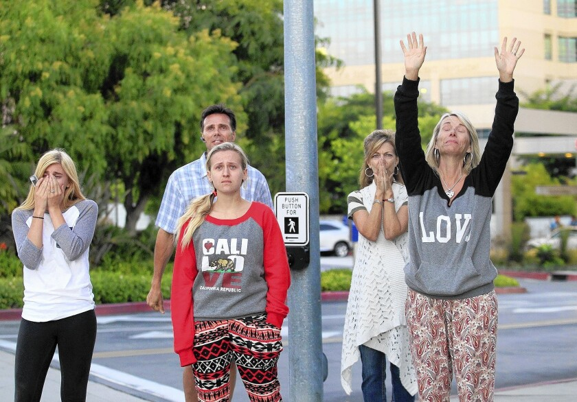Loved ones of 19-year-old Connor Eckhardt, from right, his mother Veronica Eckhardt, aunt Terri Mehrguth, sister Sabrina Eckhardt, 18, father Devin Eckhardt and close friend Jaclyn Westfall, 20, look on as a helicopter carrying Connor's heart flies off from Hoag Hospital in Newport Beach on Thursday.