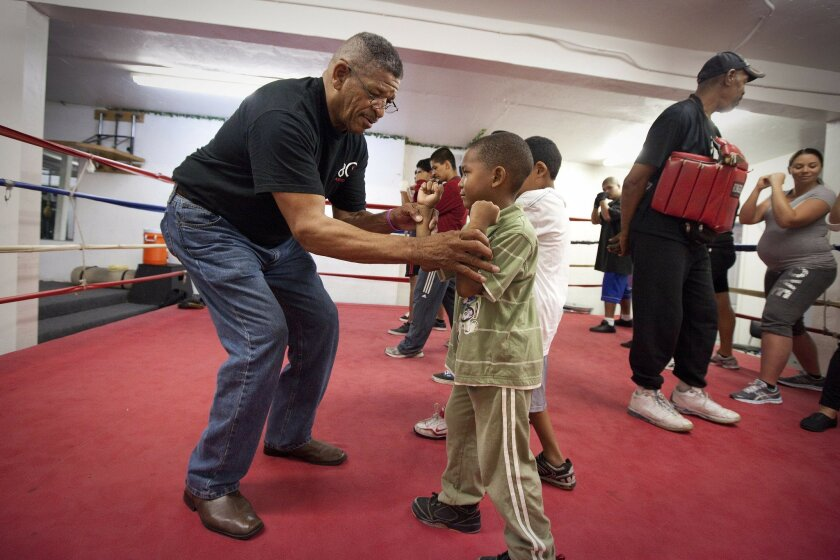 Any Body Can President Billy Moore, 62, works with 5-year-old Xavier Allen during a session at the nonprofit organization's gym in the southeastern San Diego neighborhood of Stockton.