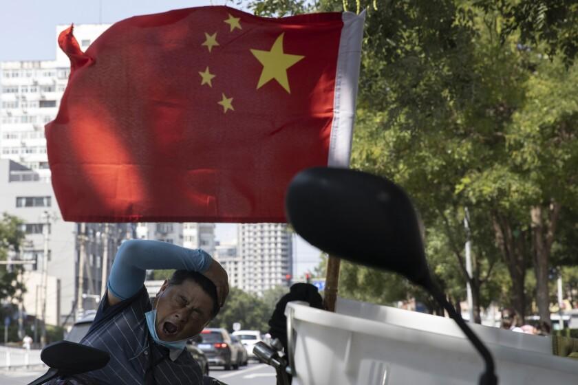 Un repartidor bosteza cerca de una bandera de China, en Beijing, el 2 de septiembre de 2020.