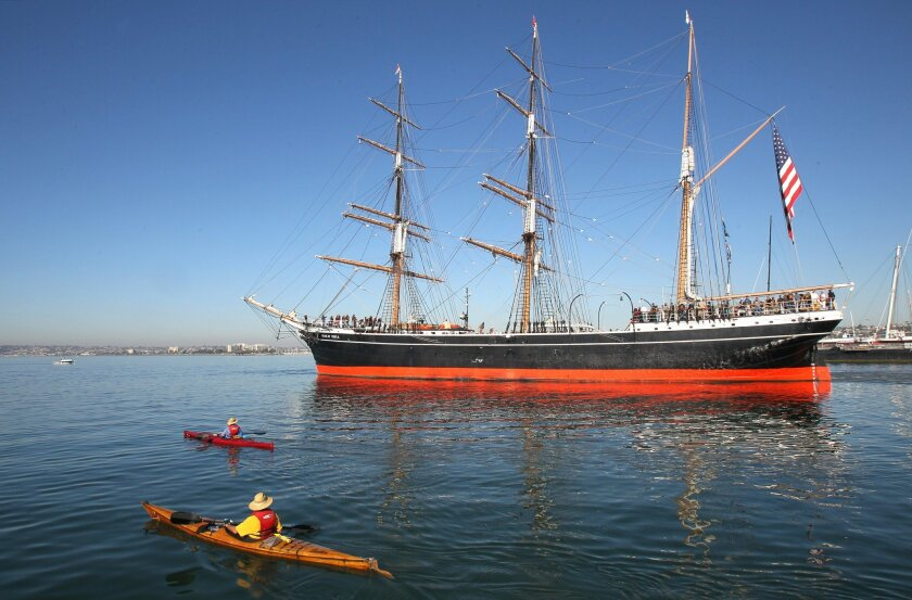 Kayakers pass by as the Star of India gets towed from the Embarcadero to the ocean for its first sailing excursion in two years.
