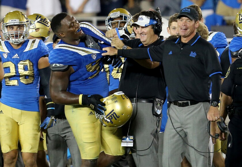 UCLA Coach Jim Mora, right, shares a light moment with defensive lineman Kenny Clark after the Bruins' 24-23 victory over BYU earlier this season.