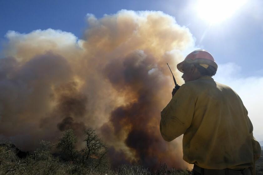 ARCHIVO _ En esta foto del 13 de octubre del 2021, un bombero mira el humo de un incendio forestal en Goleta, California. El empeoramiento de los cambios climáticos requiere que Estados Unidos haga mucho más para monitorear, aliviar y manejar los flujos de refugiados que escapan de desastres naturales, dijo el jueves el gobierno de Joe Biden, en lo que calificó del primer examen federal profundo del problema. (AP Foto/Ringo H.W. Chiu)