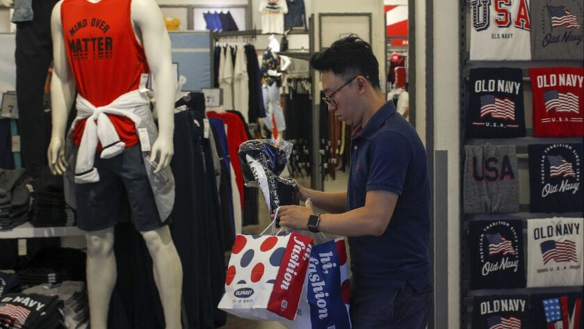 A man buys clothes from an American clothing store having a promotion sale at a shopping mall in Bei