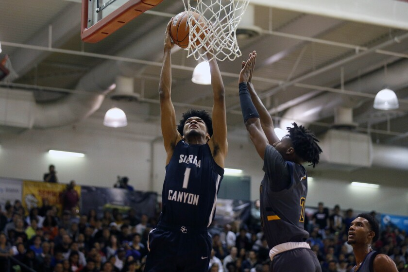 Sierra Canyon forward Ziaire Williams dunks the ball in front of Rancho Christian guard Dominick Harris during the Elite Invitational Basketball Tournament at Pasadena Community College.