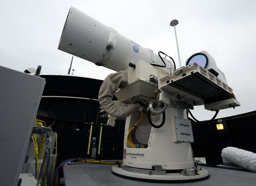 In this July 30, 2012 photo provided by the U.S. Navy, a laser weapon sits temporarily installed aboard the guided-missile destroyer USS Dewey in San Diego. The Navy plans to deploy its first laser on a ship in 2014, and intends to test an electromagnetic rail gun prototype aboard a vessel within t