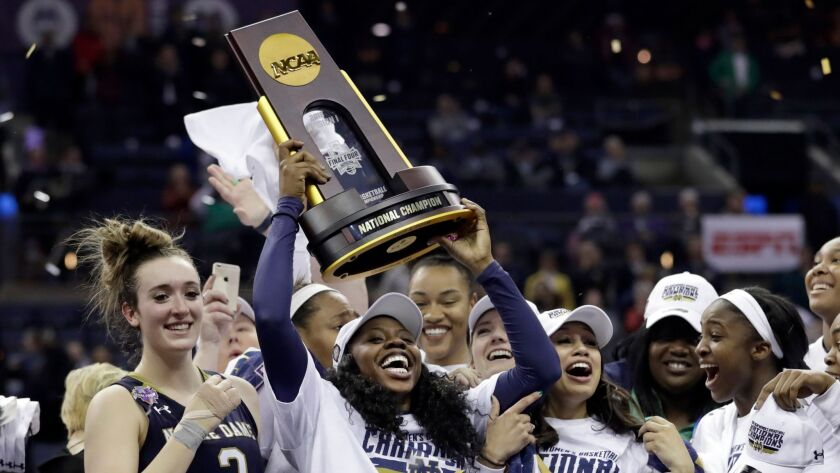 Notre Dame's Arike Ogunbowale holds the trophy after defeating Mississippi State in the final of the women's NCAA Final Four college basketball tournament.