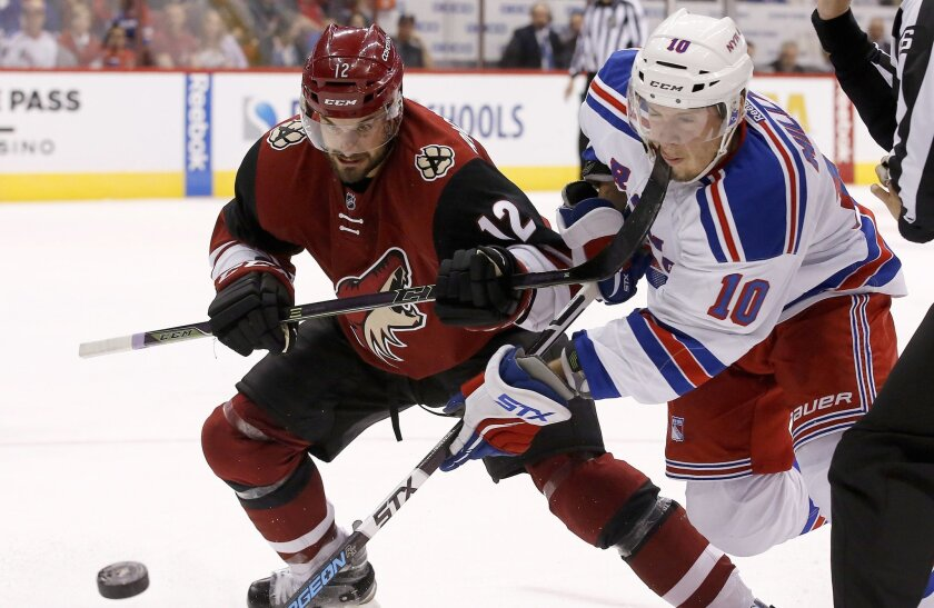 New York Rangers' J.T. Miller (10) gets a high stick to his face by Arizona Coyotes' Brad Richardson (12) during the second period of an NHL hockey game, Saturday, Nov. 7, 2015, in Glendale, Ariz. (AP Photo/Ross D. Franklin)
