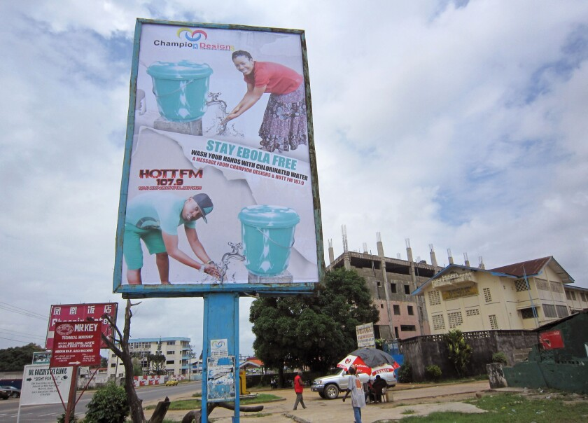 A billboard promotes hand washing to help prevent the spread of Ebola in Monrovia, Liberia. A suspected outbreak in Congo has killed 13 people but the government says it is a different strain of the virus than the one spreading through four West African countries.