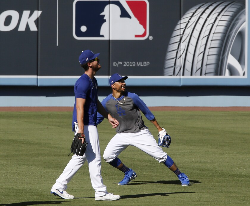 Dodgers right fielders Cody Bellinger, left, and Mookie Betts catch fly balls during practice at Dodger Stadium on Friday.