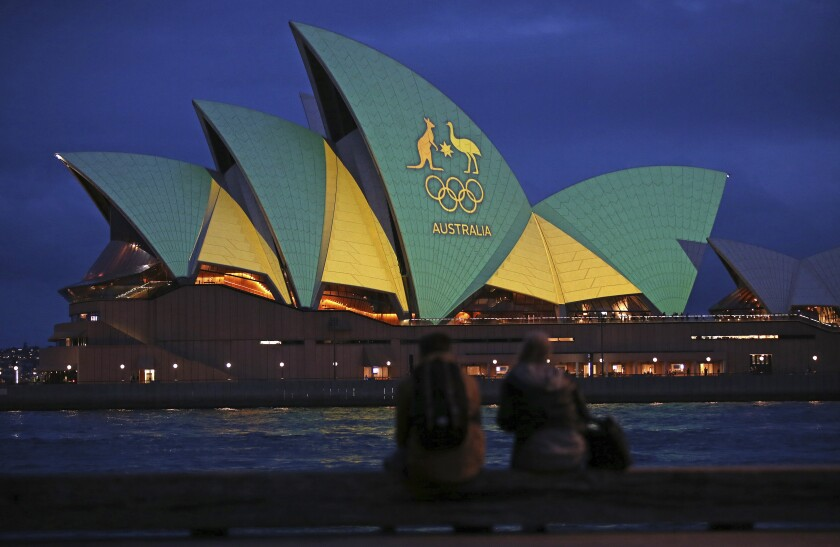FILE - In this Friday, Aug. 5, 2016, file photo, a couple sit on a dock to look at the sails of the Sydney Opera House that are illuminated with the green and gold colors of the Australian Olympic team, as Australia pushes to host the 2032 Olympics. Brisbane will be offered as the 2032 Olympics host, IOC president Thomas Bach said Thursday June 10, 2021, for International Olympic Committee members to confirm in Tokyo next month. (AP Photo/Rick Rycroft, File)