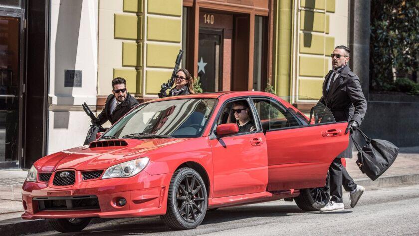 The bank heist team of Baby (Ansel Elgort, in car), Griff (Jon Bernthal, left), Darling (Eiza Gonza