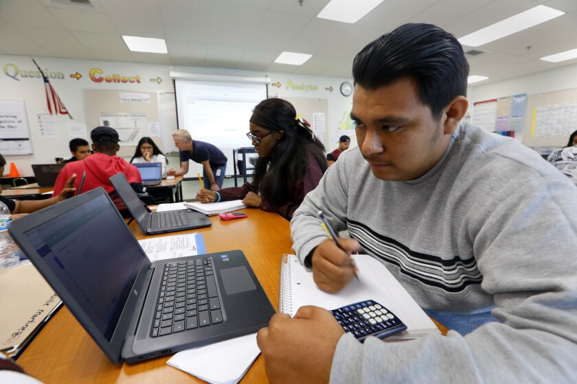 A high school senior looks at his laptop and takes notes