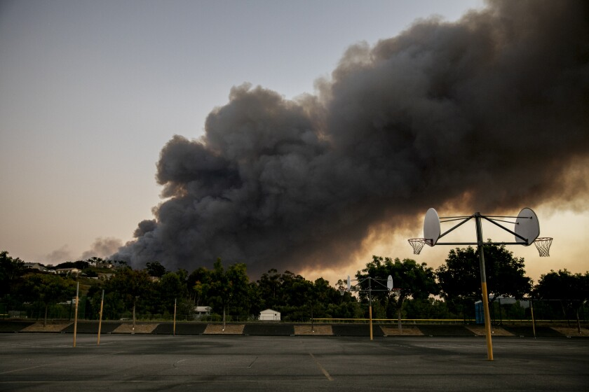 Smoke is in view from an evacuation center at MacQueen Middle School