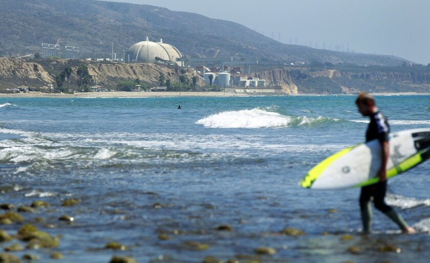 A surfer walks by with the San Onofre nuclear power plant in the background.