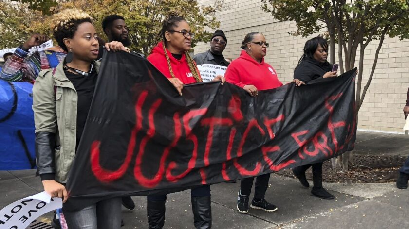"""Protestors carry a sign reading """"Justice for E.J."""" during a protest at the Riverchase Galleria i"""