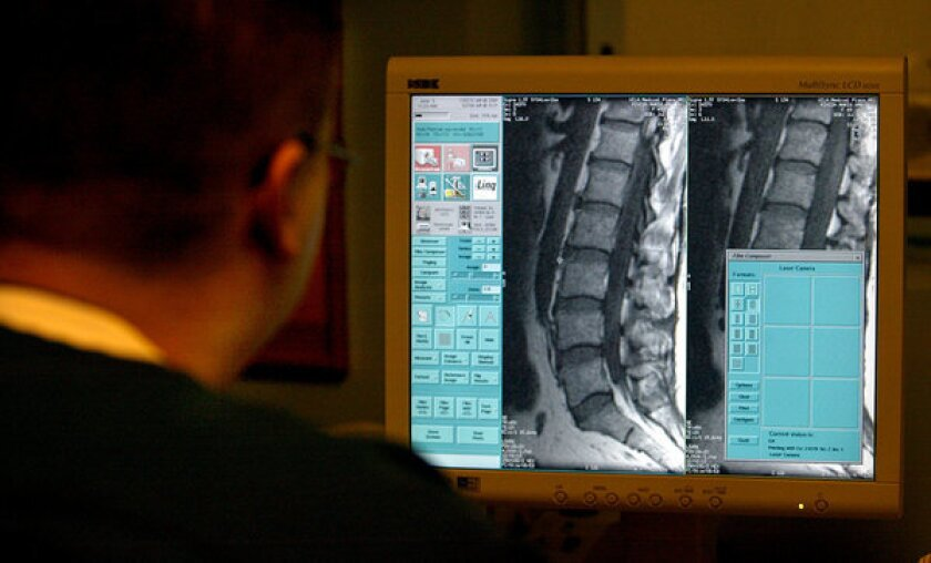 A technician views an MRI of a patient's spine. A new study says doctors are failing to follow established guidelines for the treatment of back pain. Among other problems, the study cites overuse of diagnostic imaging.