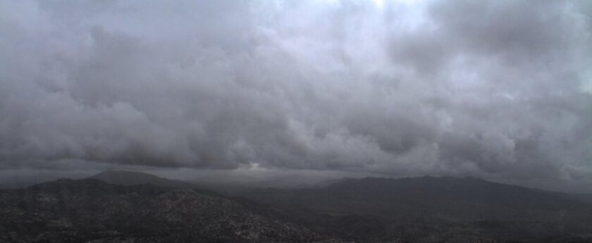 Storm clouds move off to the east Saturday near Lyons Peak.
