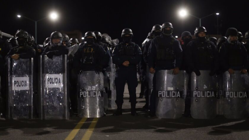Police stand outside state offices in Mexicali early Monday as officials hold talks with demonstrators to lift their two week blockade.
