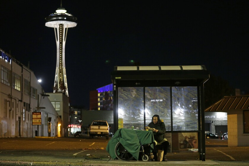 The Space Needle looms over a homeless man in Seattle. Officials estimate that 20% of the homeless population in the city live in vehicles.