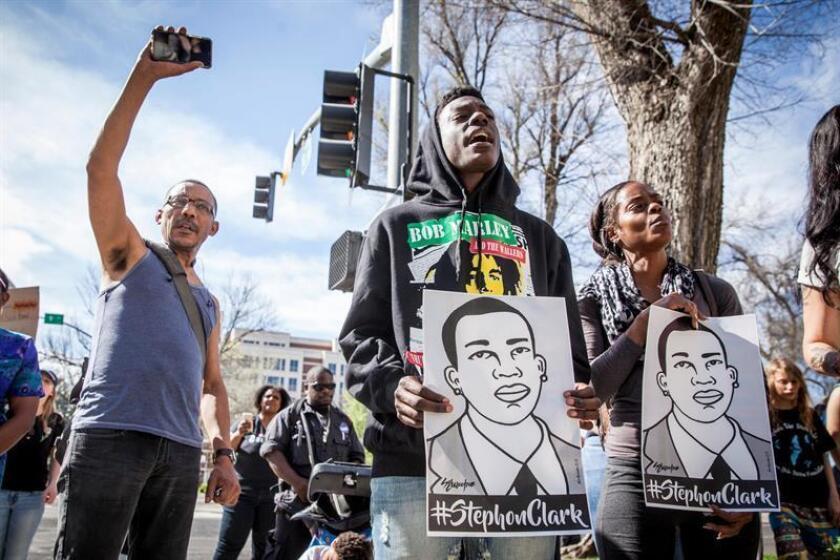 Personas sostienen carteles durante una protesta luego del funeral de Stephon Clark hoy, jueves 29 de marzo de 2018, afuera de la oficina del fiscal de distrito en Sacramento, California (EE. UU.). EFE