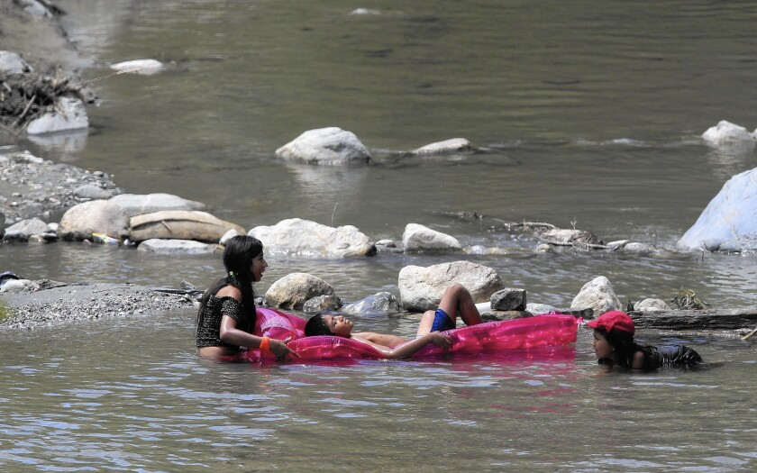 Children play in the east fork of the San Gabriel River during a heatwave.