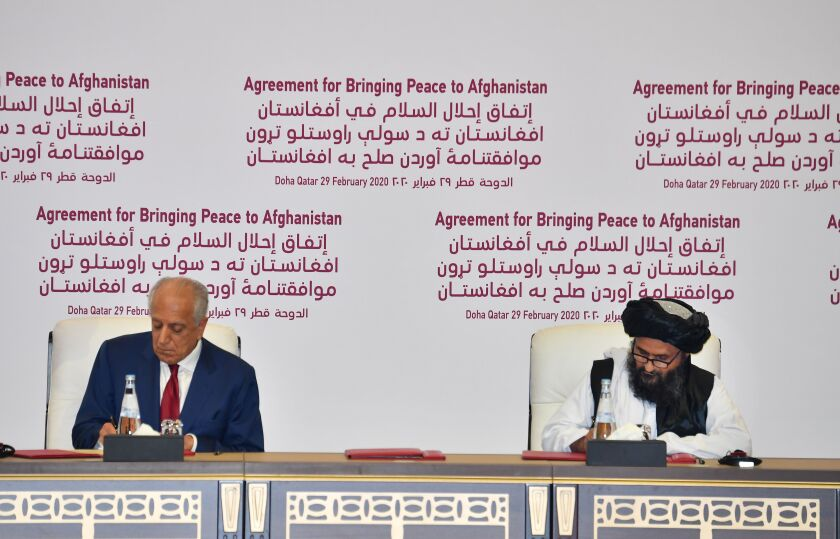 U.S. Special Representative Zalmay Khalilzad, left, and Taliban political leader Abdul Ghani Baradar sign a peace agreement in Doha, Qatar on Feb. 29, 2019.