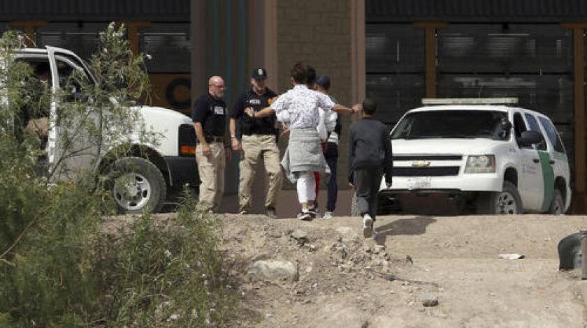 En esta imagen de archivo, tomada el 4 de julio de 2019, un grupo de solicitantes de asilo cruza la frontera entre El Paso, Texas, y Juárez, Chihuahua, México. (Mark Lambie/The El Paso Times via AP)
