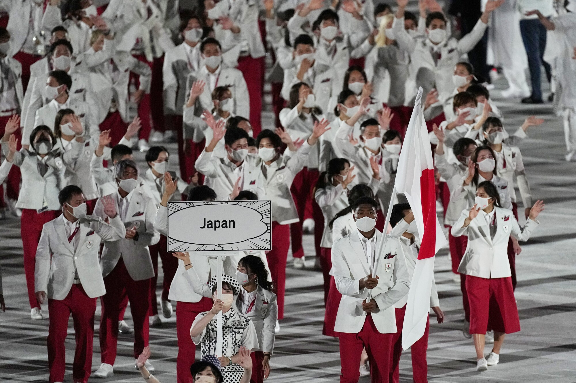 Yui Susaki and Rui Hachimura, of Japan, carry their country's flag during the opening ceremony
