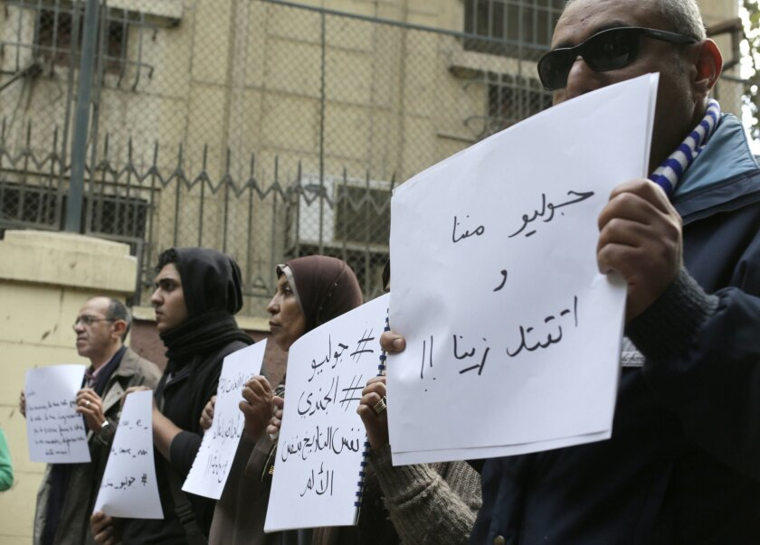 Mourners hold slogans at a vigil for slain Italian graduate student Giulio Regeni in front of the Italian embassy in Cairo, Egypt, Saturday, Feb. 6, 2016. Regeni disappeared on Jan. 25, the anniversary of Egypt's 2011 uprising. He was found this week with multiple stab wounds, cigarette burns and o