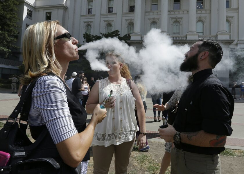 Kari Hess, left, co-owner of Nor Cal Vape, in Redding, Calif., celebrates with Jackie Voisione, center, and Michael Ventura, right, an e-liquid manufacturer from San Diego, after a bill to regulate E-Cigarettes stalled in an Assembly Committee, at the Capitol Wednesday, July 8, 2015, in Sacramento,