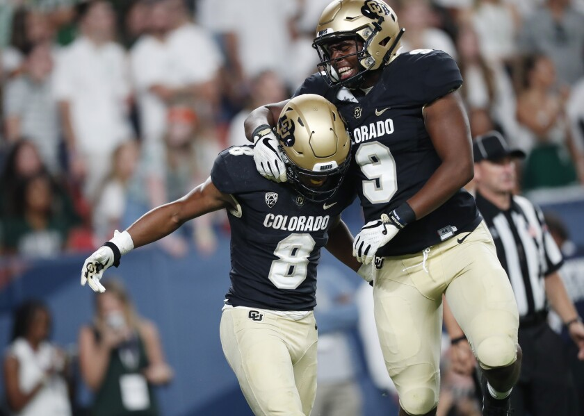 Colorado tight end Jalen Harris, right, celebrates with running back Alex Fontenot, who scored a touchdown against Colorado State in the third quarter on Friday in Denver.