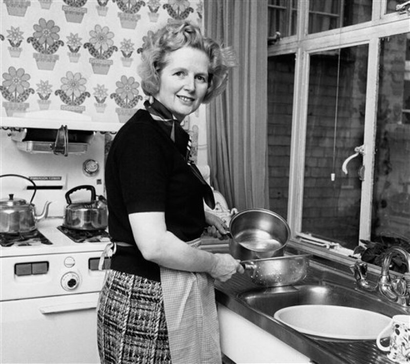 """FILE - Feb, 1, 1975 file photo of the them Conservative Member of Parliament Margaret Thatcher, in her Chelsea home kitchen. She was Britain's first female leader, a strong woman who battled her way to the top of a male-dominated political system _ but don't call Margaret Thatcher a feminist. The former prime minister, who died Monday aged 87, rejected the label _ """"I owe nothing to women's lib,"""" she once said _ and she leaves a contested legacy for women. (AP Photo/ PA/File) UNITED KINGDOM OU"""