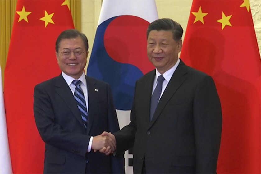 In this image from video, South Korean President Moon Jae-in, left, shakes hands with his Chinese counterpart Xi Jinping as they pose for photographers ahead of their meeting at the Great Hall of the People in Beijing, Monday, Dec. 23, 2019. The leaders of China, Japan and South Korea are holding a trilateral summit in China this week amid feuds over trade, military maneuverings and historical animosities. Most striking has been a complex dispute between Seoul and Tokyo, while Beijing has recently sought to tone down its disagreements with its two neighbors. (AP Photo)