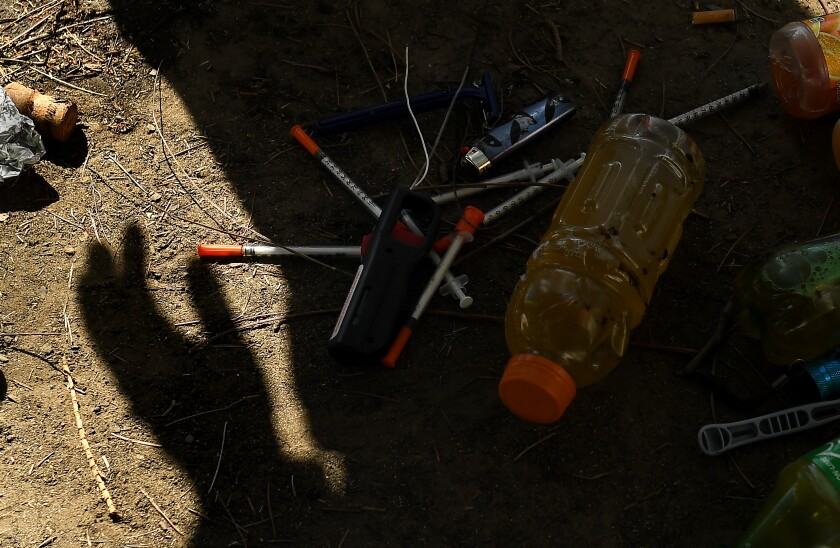 A shadow of a work crew member stands over syringes and other items.