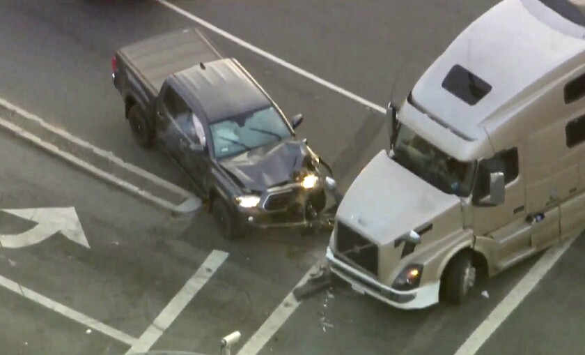 A pickup truck and semitruck are damaged after a crash.