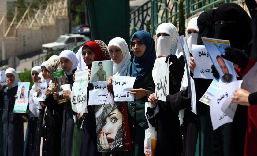 Palestinian protesters hold pictures of family members as they demonstrate in the West Bank city of Nablus, demanding the release of prisoners on hunger strike held in Israeli jails.