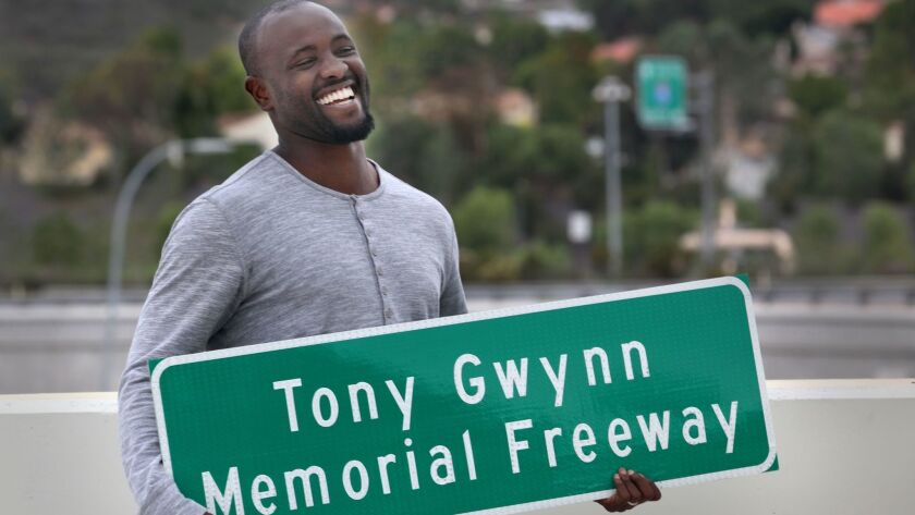Tony Gwynn Jr. smiles broadly as he holds a replica sign made for him and his family, presented to them by Caltrans employees Monday during a ceremony unveiling new freeway signs namiing a section o