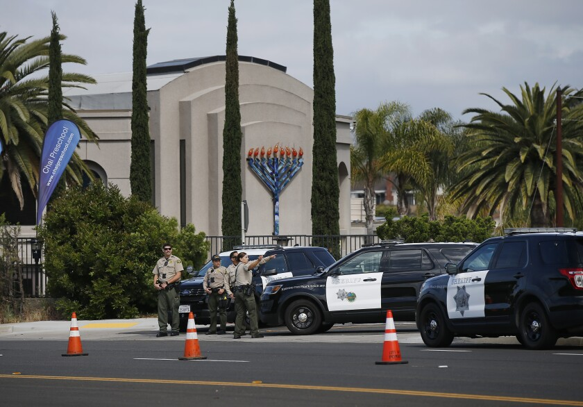 Sheriff's deputies stand outside the Chabad of Poway synagogue the day after the shooting there