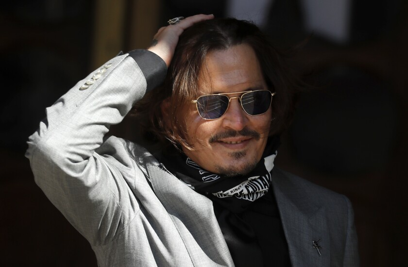 """FILE - In this file photo dated Tuesday, July 28, 2020, US Actor Johnny Depp arrives at the High Court in London during his case against News Group Newspapers over a story published about his former wife Amber Heard, which branded him a 'wife beater'. A British judge is set to deliver his judgement in writing on Monday Nov. 2, 2020, deciding whether a tabloid newspaper defamed Depp by calling him a """"wife beater."""" (AP Photo/Frank Augstein, FILE)"""
