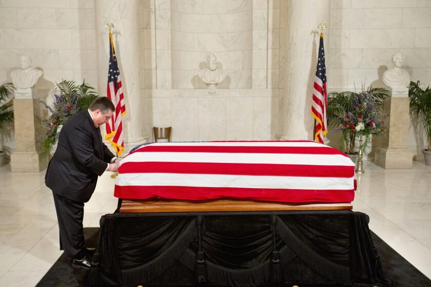 Un empleado de una casa funeraria arregla la bandera estadounidense que cubre el féretro del magistrado de la Corte Suprema, Antonin Scalia, en la Gran Sala del lugar en Washington. La puerta fue abierta después para que entrara el público a rendir homenaje al magistrado. (AP Foto/Jacquelyn Martin, Pool)