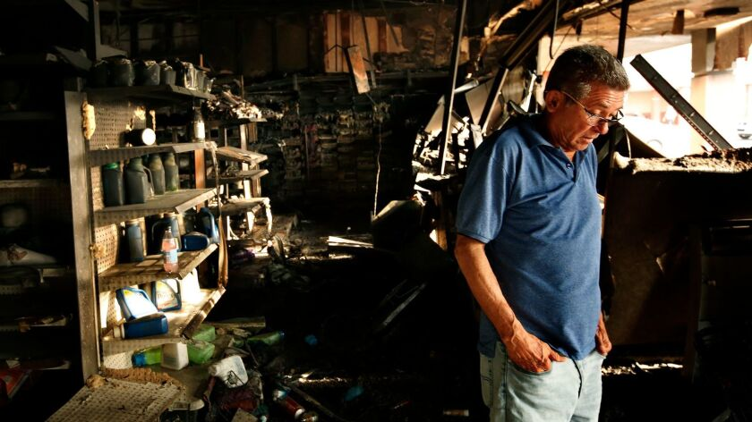 A cafe owner stands in the ruins of a shopping area in San Juan on Monday. A nearby drugstore had be