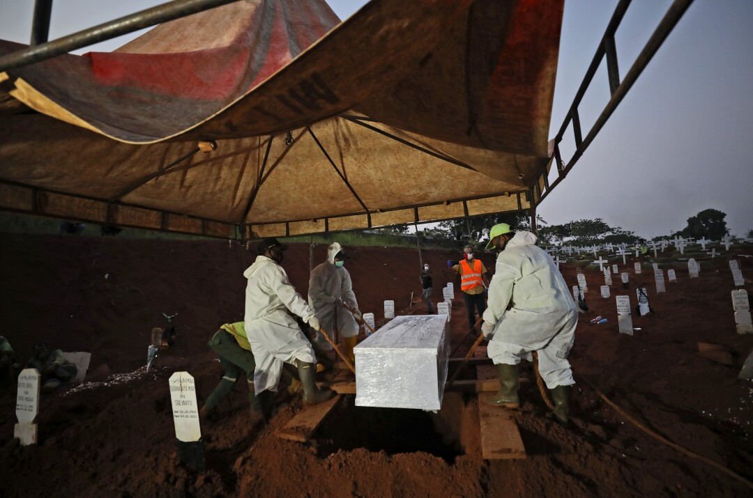 Workers lower a coffin containing the body of a suspected COVID-19 victim into a grave at Pondok Ranggon cemetery.