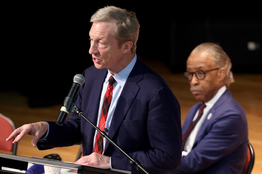 Democratic presidential candidate Tom Steyer speaks as the Rev. Al Sharpton looks on Wednesday at a breakfast in North Charleston, S.C.