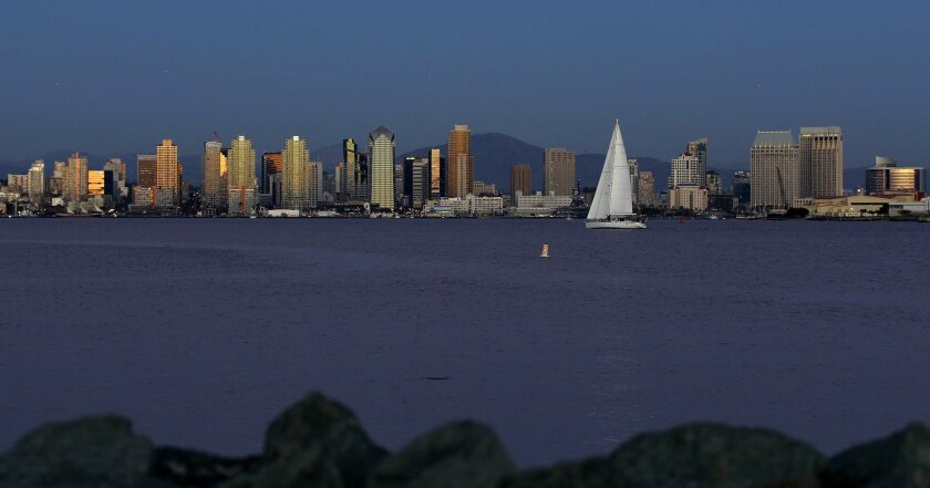 A sailboat sails in San Diego Bay as the sun reflects on buildings at sunset on Wednesday, March 21, 2012.