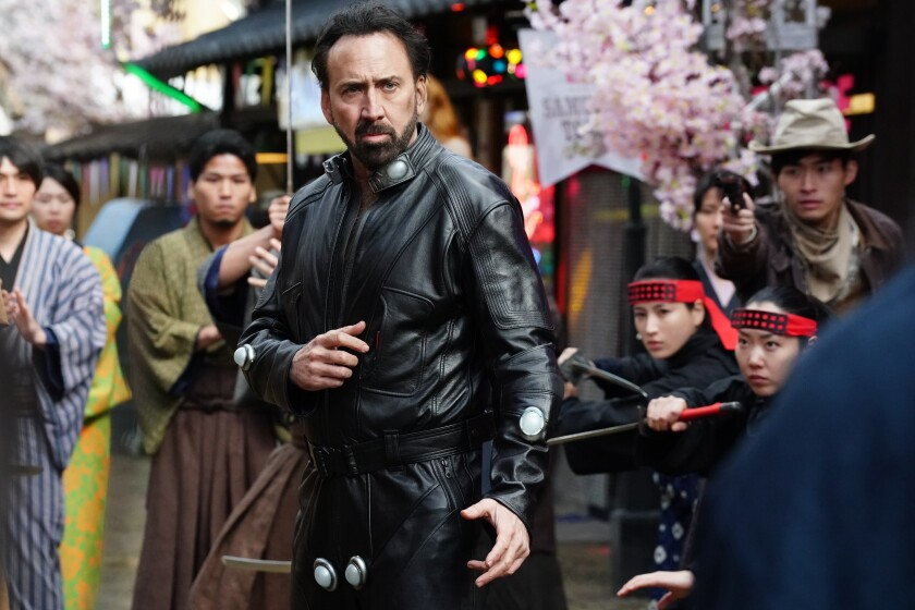 A man in leather strikes a martial arts pose as people look on