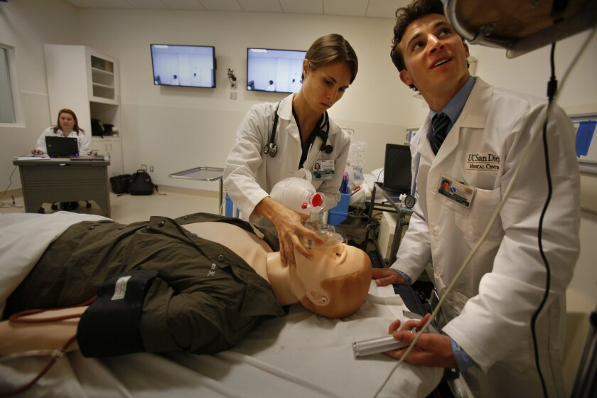UCSD emergency medical resident physician Christanne Coffey gives oxygen to a sophisticated electronic mannequin while resident Chad Valderrama checks its vital signs in the new Medical Education and Telemedicine Center at the UCSD School of Medicine. Behind them, physician Leslie Oyama controls the mannequin.
