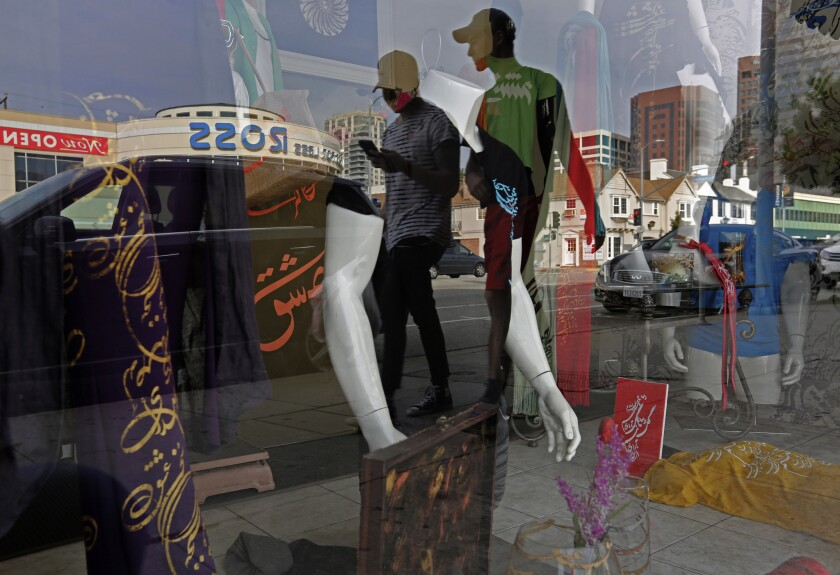 People are reflected in a storefront as they walk down Westwood Boulevard, in Persian Square, in Los Angeles.