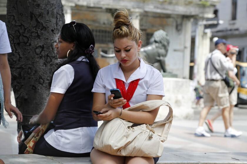 Una mujer utiliza dos teléfonos móviles para conectarse a internet en uno de los nuevos puestos de wi-fi públicos en La Habana, Cuba, el jueves 2 de julio de 2015. (AP Foto/Desmond Boylan)